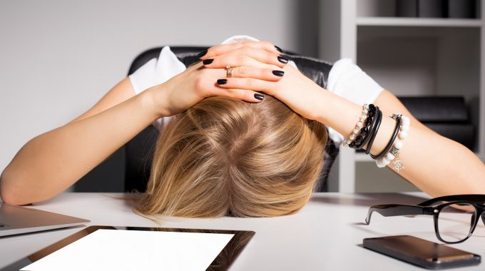 Woman With Head On Desk After Making Event Planning Mistakes